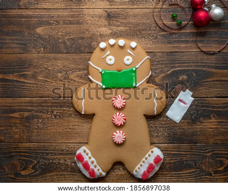 Gingerbread cookie decorated with icing and candy, wearing a green icing mask taken from an overhead view. with a hand sanitizer bottle made from white icing beside it. set on wooden table. copy space