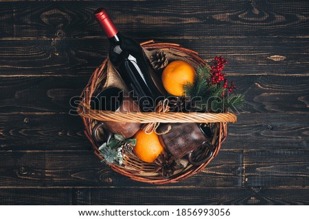 Bottle of red wine in Christmas gift basket. #1856993056