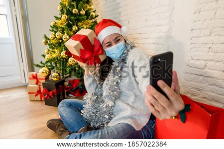 Happy woman with face mask home alone in lockdown using smart mobile cell phone, celebrating Virtual christmas video calling family and friends. COVID-19 Virtual holidays and online social gathering. #1857022384