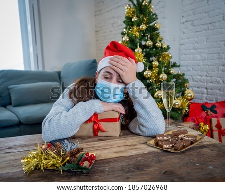 Sad woman with mask home alone in self isolation at christmas feeling depressed mourning and missing family and friends. COVID-19 Lockdown and quarantine during winter holidays and mental health. #1857026968