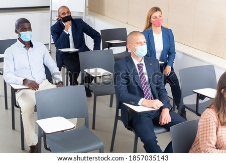 International group of business people wearing protective face masks listening to presentation in conference room. Concept of precautions and social distancing in COVID 19 pandemic.. Royalty-Free Stock Photo #1857035143