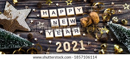 Banner.Happy New Year 2021. A symbol from the number 2021 with Golden balls, stars, sequins and a beautiful bokeh on a wooden background. The concept of the celebration. Royalty-Free Stock Photo #1857106114