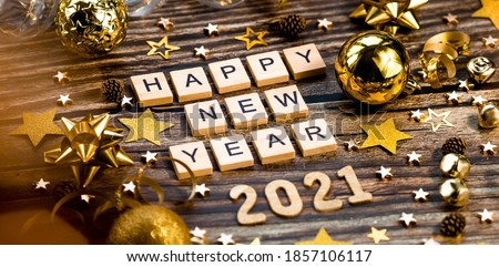 Banner.Happy New Year 2021. A symbol from the number 2021 with Golden balls, stars, sequins and a beautiful bokeh on a wooden background. The concept of the celebration. Royalty-Free Stock Photo #1857106117