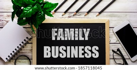 FAMILY BUSINESS is written in white on a black board next to a phone, notepad, glasses, pencils and a green plant.