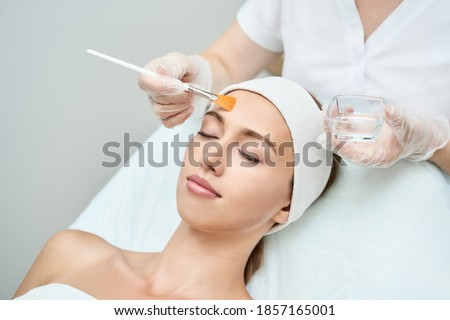 Cosmetology beauty procedure. Young woman skin care. Beautiful female person. Rejuvenation treatment. Facial chemical peel therapy. Clinical healthcare. Doctor hand. Dermatology cleanser. Royalty-Free Stock Photo #1857165001