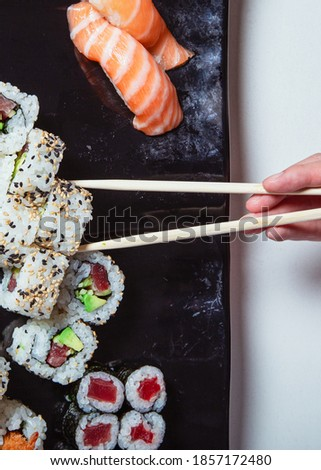 Top view of woman's hand holding sushi sticks. Sushi rolls laid out on a black plate. Vertical picture