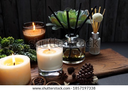 nice aromatic scented candle glass and reed diffusers  lighting on wooden holder on black wooden table with dried potpourri , herbs and spices pinecone in living room during Christmas new year party Royalty-Free Stock Photo #1857197338