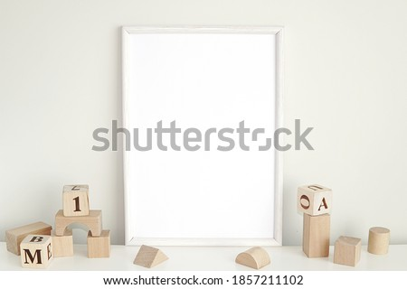 White frame mockup for nursery or kids room, blank photo frame and wooden cubes. Royalty-Free Stock Photo #1857211102