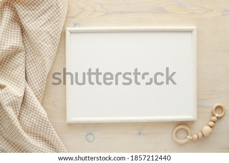 Nursery frame mockup, horizontal white wooden frame mock up for baby room art, pregnancy announcement, top view, flat lay. Royalty-Free Stock Photo #1857212440