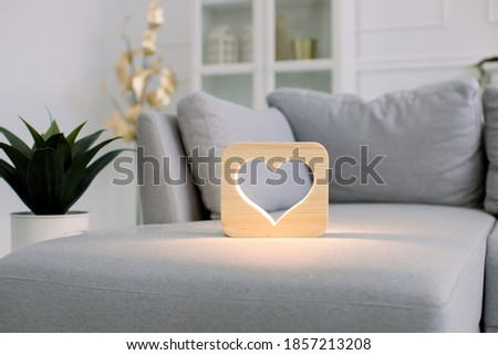 Wooden night lamp with heart picture, on gray monochrome sofa, at stylish light home living room interior. Home decor and lamps. Wooden hand made accessories
