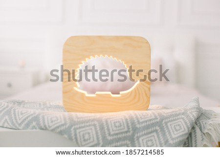 Close up of cozy wooden night lamp with hedgehog cut out picture, on gray blanket at cozy light bedroom interior. Wooden decorations and accessories at home interior