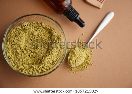 Henna mhendi colorant powder in a glass bowl and a wooden comb on a beige background top view. Ayurvedic hair care products. Natural care and hair coloring.