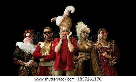 Medieval people as a royalty persons in vintage clothing and modern eyewear using devices on dark background. Concept of comparison of eras, modernity and renaissance, baroque style. Creative collage. Royalty-Free Stock Photo #1857261178