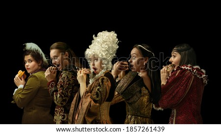 Medieval people as a royalty persons in vintage clothing eating burger, fast food on dark background. Concept of comparison of eras, modernity and renaissance, baroque style. Creative collage. Royalty-Free Stock Photo #1857261439