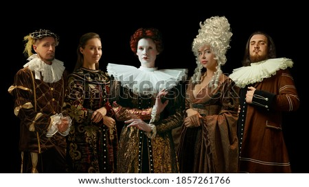Medieval people as a royalty persons in vintage clothing posing proud and confident on dark background. Concept of comparison of eras, modernity and renaissance, baroque style. Creative collage. Royalty-Free Stock Photo #1857261766