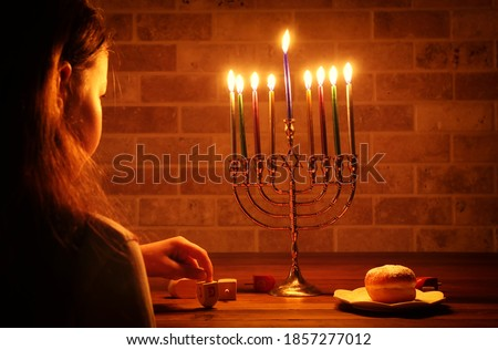 Low key image of jewish holiday Hanukkah background with girl looking at menorah (traditional candelabra) and burning candles