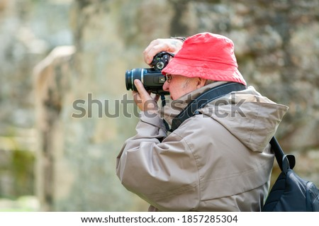 An elderly man uses a camera in ancient ruins.