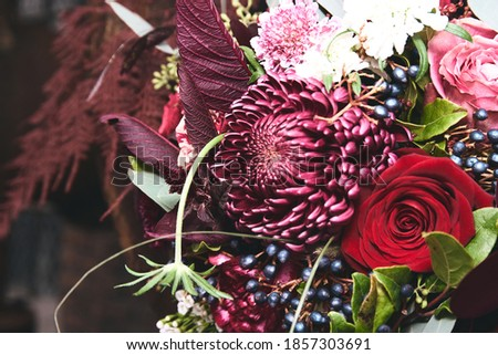 Dark magenta flower arrangement  in a rusty tube with in an industrial flair