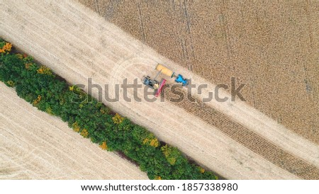 Aerial view of combine loading off corn grains into tractor trailer. Flying over agricultural machines working in farmland. Harvesting concept. Rotating shot.