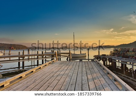 Single sailboat moored at the end of a peaceful wooden pier with the tranquil archipelago all around, on a flat calm, balmy late summer's evening in Sweden. Royalty-Free Stock Photo #1857339766