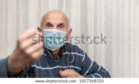 angry aggressive elderly man wearing face mask showing big fist self isolation and coronavirus concept white background Royalty-Free Stock Photo #1857368320