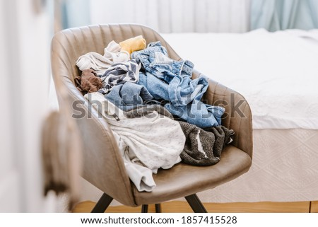 Pile of unfolded dirty clothes for laundry on the chair. Heap of used clothes for donation and recycling. Concept of minimalism, mess and wardrobe cleaning Royalty-Free Stock Photo #1857415528