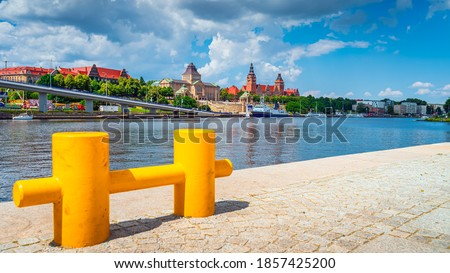 Large, defocused yellow mooring cleat on pier with view on boats, National Museum, Chrobry Shafts and old passport office building in Szczecin, Poland Royalty-Free Stock Photo #1857425200