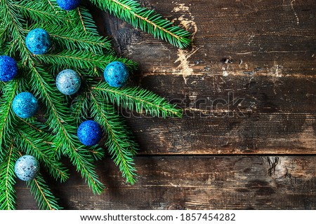 christmas festive background of spruce sprigs decorated with blue christmas toys on an old wooden surface