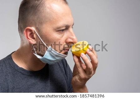 Anosmia or smell blindness, loss of the ability to smell, one of the possible symptoms of covid-19, infectious disease caused by corona virus. Man Trying to Sense Smell of a Lemon Royalty-Free Stock Photo #1857481396