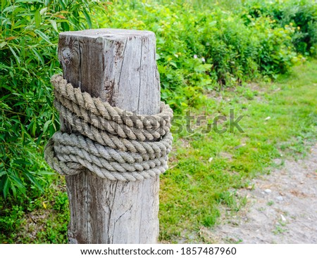 Large wooden post with thick rope wrapped around, near green vegetation. Royalty-Free Stock Photo #1857487960