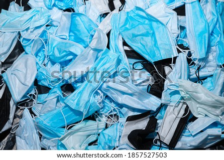 Medical masks on the table. Pile of used personal protective equipment PPE. Pollution by surgical masks during the coronavirus pandemic. A lot of Covid-19 plastic waste and garbage, disposable masks.  Royalty-Free Stock Photo #1857527503