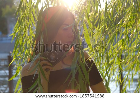 Retro Film camera in hands of asian girl posing in willow branches in sunset time. Vintage romantic looking picture.