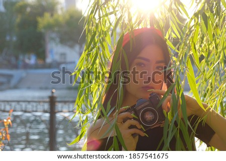 Vintage Film camera in hands of cute asian girl posing in willow branches in sunset time. Vintage romantic looking picture.