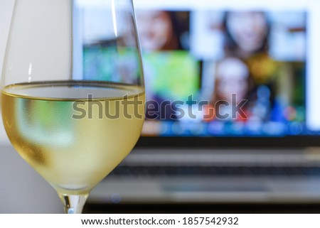 filled glass of wine in front of a laptop