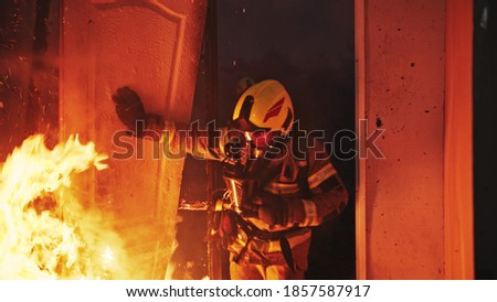 Firefighter entering through the door of the burning house. High quality photo Royalty-Free Stock Photo #1857587917