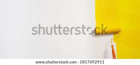 Roller Brush Painting, Worker painting on surface wall  Painting apartment, renovating with yellow color  paint. Leave empty copy space white to write descriptive text beside. Royalty-Free Stock Photo #1857692911