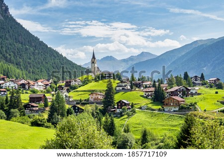 Beautiful Schmitten village at Albula pass in Grisons, Graubuenden, Switzerland with view of houses on green grassy hills, a lovely church on hilltop and majestic mountains in background Royalty-Free Stock Photo #1857717109