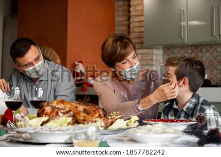 Family sitting at the Christmas Thanksgiving table at home in the year of the Coronavirus Pandemic. Grandmother adjust the surgical mask to her grandson. New rules, Covid outbreak, lockdown. #1857782242
