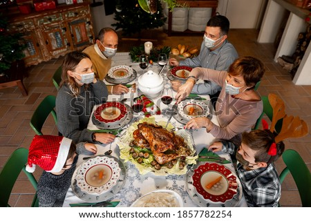 Zenith angle of a Family gathered around the table at Christmas Thanksgiving dinner on 2020. Family members wear surgical masks to comply with the new health regulations. Covid quarantine, lockdown. #1857782254