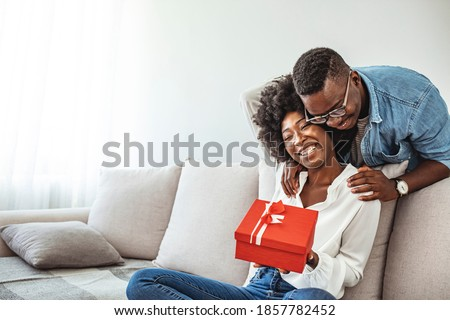 Xmas surprise. Afro man giving Christmas present to girlfriend. Thankful afro woman with christmas gift hugging husband at home. Presenting gift as Christmas eve tradition