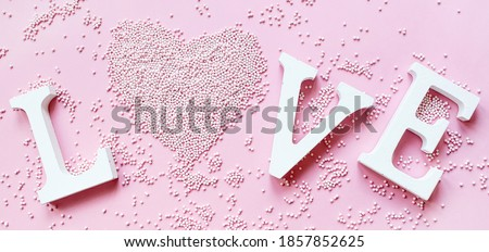 Banner.The word love in white letters on a trendy pink background. Happy Valentine's Day, Mother's Day, March 8, World Women's Day holiday card concept. Flat lay.  #1857852625