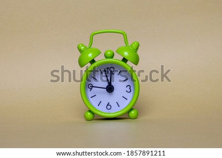 alarm clock on a beige background reminder of the time holiday is coming bright green assistant in the distribution of time working time leisure time everything is under control with the clock