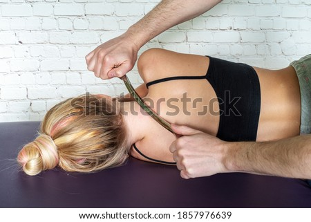 IASTM treatment, girl receiving soft tissue treatment on her neck with stainless steel tool Royalty-Free Stock Photo #1857976639