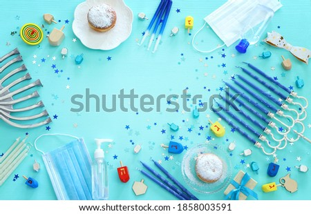 Image of jewish holiday Hanukkah with menorah (traditional Candelabra), donut, wooden dreidel (spinning top). Coronavirus prevention concept, medical mask and and sanitizer gel