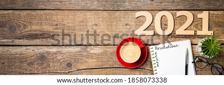 New year resolutions 2021 on desk. 2021 resolutions with notebook, coffee cup, succulent,  eyeglasses on wooden background. Goals, plan, strategy, list, idea concept. New Year 2021 template,copy space #1858073338