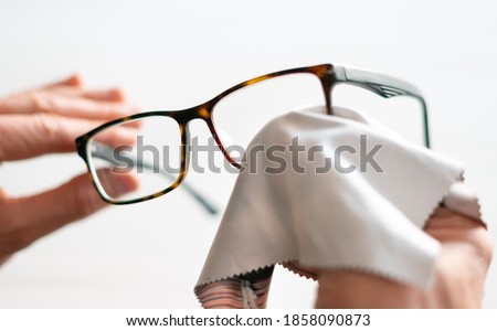 Cleaning glasses. A man wipes his glasses with a cloth. Selective focus. Royalty-Free Stock Photo #1858090873