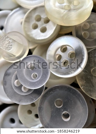 White, off-white and cream antique or vintage sewing buttons: Celluloid Buttons, Bakelite Buttons, Lucite Buttons, Vegetable Ivory, metal, China, glass, and mother of pearl.  Royalty-Free Stock Photo #1858246219