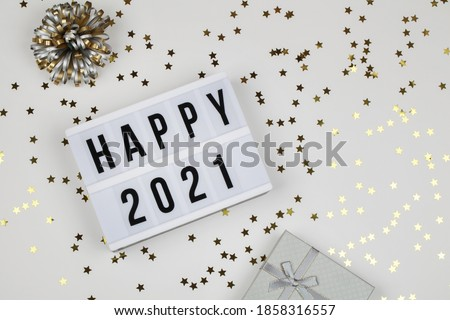 lightbox with words happy 2021, gift box and holiday confetti on white background. top view. New year celebration. Happy New Year 2021 concept.