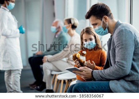 Father and daughter wearing protective face masks while surfing the net on digital tablet in a hallway at the hospital.  Royalty-Free Stock Photo #1858356067