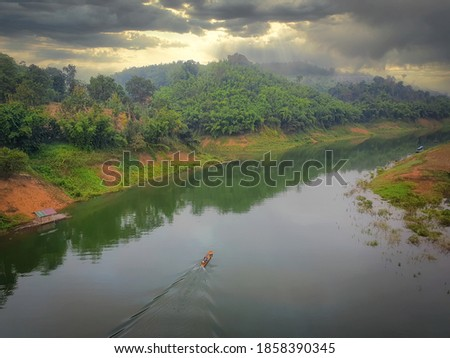 Boats sail along the Songkalia River during sunrise time. Taken picture at Sangkhlaburi District, Kanchanaburi Province in Thailand.